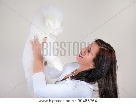 Glamorous woman in white with white fluffy dog