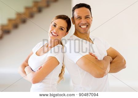 portrait of fit mid age couple with arms crossed