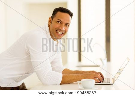 good looking mid age man with laptop in kitchen