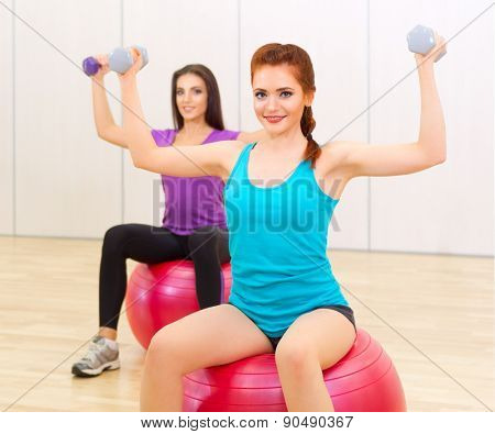 Two young girls doing gymnastic exercises at sports hall