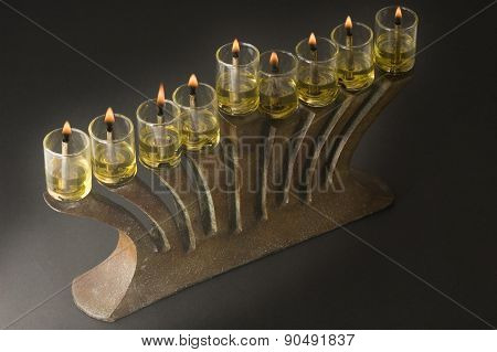 antique menorah lit with olive oil