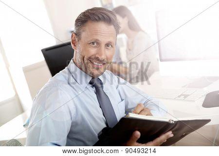 Portrait of handsome businessman holding agenda