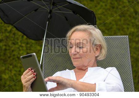 Senior Serene Woman Using A Black Tablet Pc