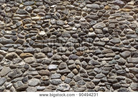 Ancient wall of gray rounded natural stones