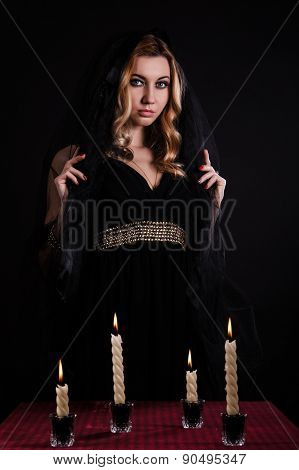Young Woman With Candles In Darkness