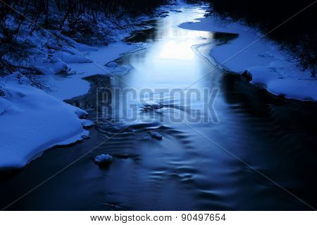 Icy blue river on cold winter evening