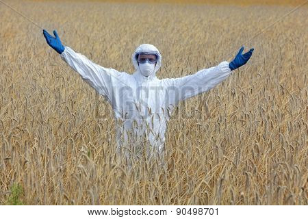 Happy biotechnology engineer in white uniform, mask, goggles on field of crops