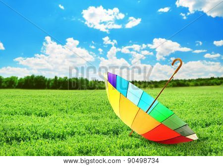 Colorful umbrella on green field, outdoors