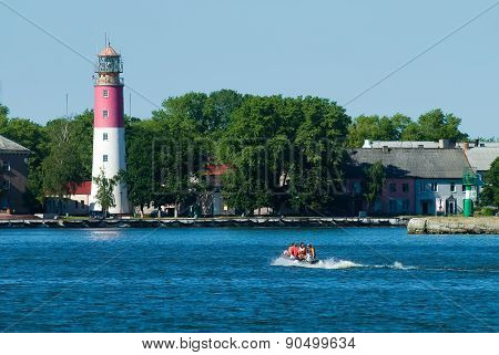 People in rubber boat and lighthouse is Baltiysk