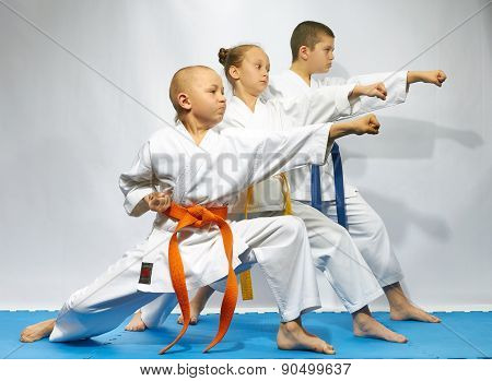 Straight punch arm are performing sportsmens on a blue mats