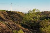 stock photo of ravines  - Dirt roads in the ravine with the electric pole in the early spring - JPG