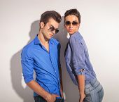 picture of young woman posing the camera  - Young fashion couple posing together againt a grey wall - JPG