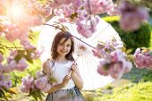 picture of japan girl  - Smiling little brunette girl looking forward with japanese umbrella in pink cherry blossom in daylight in the garden horizontal picture - JPG