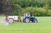 image of fertilizer  - agricultural machine fertilizes a green field in spring - JPG