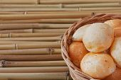 picture of brazilian food  - Brazilian snack cheese bread (pao de queijo) in wicker basket on bamboo table. Selective focus. Copy space ** Note: Shallow depth of field - JPG