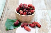 stock photo of mulberry  - Fresh mulberry in wooden bowl on wooden background - JPG