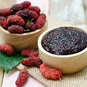 picture of mulberry  - home made mulberry jam in wooden bowl and some fresh fruits and - JPG