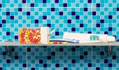 stock photo of personal hygiene  - Personal hygiene products on glass shelves on blue background - JPG