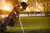 picture of golf bag  - Close up of golf bag with two golf player on green in background at sunset - JPG