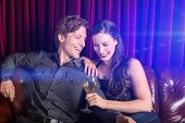 picture of flirty  - Young flirty couple with wine at a club lounge - JPG