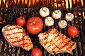 stock photo of rib eye steak  - Pork Rib Steaks Tomato And Mushrooms On Hot Flaming BBQ Charcoal Grill - JPG