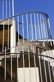 stock photo of spiral staircase  - External metal spiral staircase fire escape in sunlight - JPG