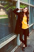 stock photo of blouse  - Young woman portrait with long brown hair dressed in black trenchcoat and yellow blouse - JPG