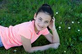 stock photo of  preteen girls  - Happy casual preteen girl lying in the grass - JPG