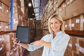 stock photo of self-storage  - Mature student pointing to tablet against shelves with boxes in warehouse - JPG