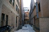 stock photo of dumpster  - An alley between large buildings - JPG