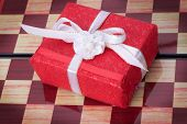 stock photo of chessboard  - red little gift box on a chessboard - JPG