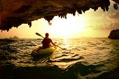 foto of cave woman  - Young lady paddling the kayak in a sea near the cave exit - JPG