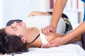 picture of physiotherapy  - young woman in pain lying while getting a massage from specialist concept of physiotherapy - JPG