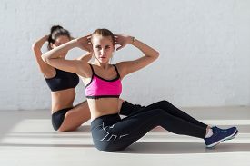 picture of abdominal  - Women doing abdominal crunches stretching exercise hands behind heads at yoga class in fitness studio looking at camera - JPG