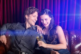 foto of flirty  - Young flirty couple with wine at a club lounge - JPG