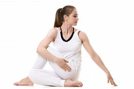 stock photo of half  - Young fitness model in white sportswear doing yoga or pilates training Half lord of the fishes pose Ardha Matsyendrasana side view studio shot isolated - JPG