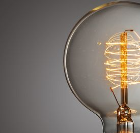 stock photo of glow  - Close up glowing vintage light bulb on gray - JPG