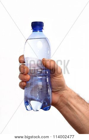 Hand holding mineral water bottle on white background.