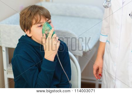 Young boy and nurse making inhalation with nebuliser in exam room