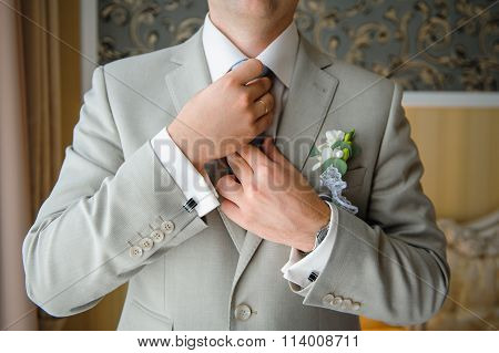 Man In A Suit Straightens His Tie With Cufflinks On Their Sleeves