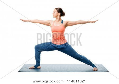 Beautiful sporty fit yogini woman practices yoga asana Virabhadrasana 2 - warrior pose 2 isolated on white