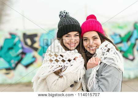 Two happy teenage girls with beanies and shawl in winter. No retouch