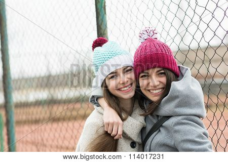 Two happy teenage girls in beanies hugging