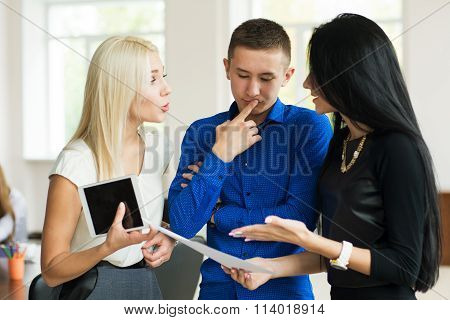 Team Of Three Successful Young Business People Discussing In Office