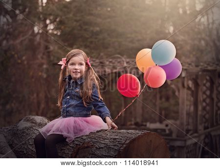 moody portait of a little girl sitting on a tree and holding colorful baloons