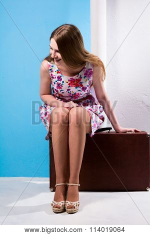 Girl In Dress Sitting On A Suitcase Tilting Head