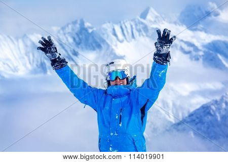 Laughing skier in helmet and blue winter outfit with his hands up, mountains in the background