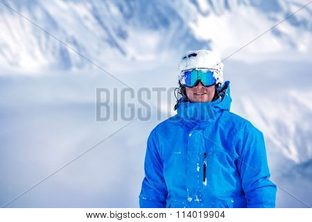 Portrait of a male tourist in ski outfit, goggles and helmet at the winter resort