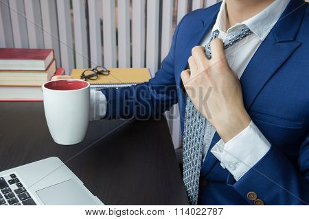 Businessman Loosening Necktie Carries Coffee Cup