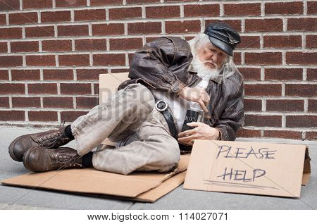 Poor senior man sitting on cardboard with a bottle of whiskey. Old man drunk with white beard sitting  on footpath holding a bottle of whiskey.